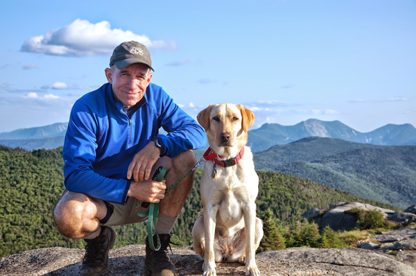 guy with a puppy on a mountain